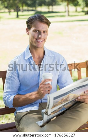 Smiling man sitting on park bench drinking coffee and reading paper on a sunny day