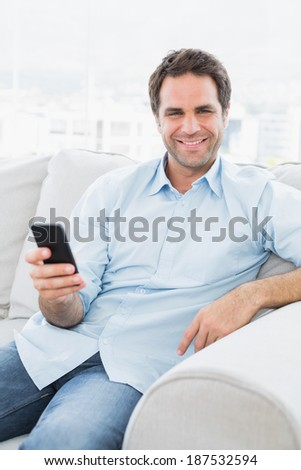 Smiling man sitting on the couch sending a text with smartphone at home in the living room - stock photo