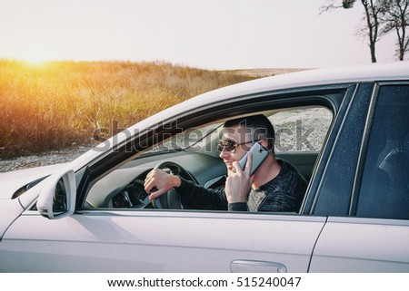 Smiling Man Speak on Smart Phone in White Car. The businessman successful driving his car and speaking on the cellphone. Driving in the evening at sunset.