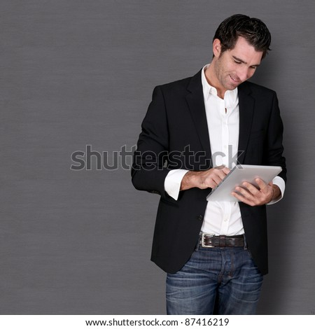 Smiling man standing on dark background - stock photo