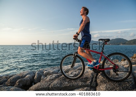 Smiling man standing with a red bicycle on the rock near sea - stock photo