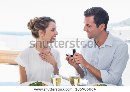 Smiling man surprising woman with a wedding ring at lunch table at home - stock photo