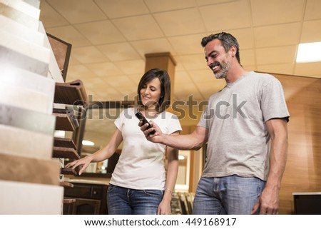 Smiling man taking shot of ceramic tile for bathroom near his cheerful woman choosing tile.