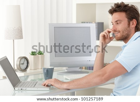 Smiling man talking on mobile phone while using laptop computer at desk in study. Blank space on screens for your logo or image.