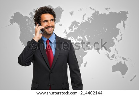 Smiling man talking on the phone in front of a world map - stock photo