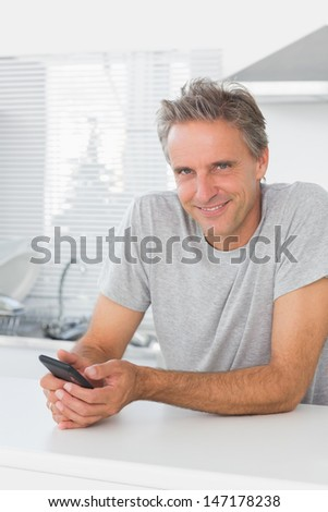 Smiling man texting in kitchen looking at camera - stock photo