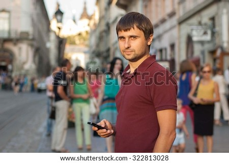 Smiling man using a smartphone on the street