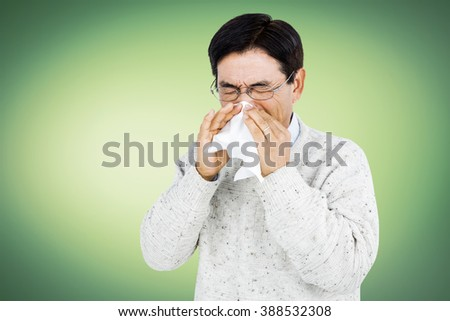 Smiling man using a tissue while sneezing - stock photo
