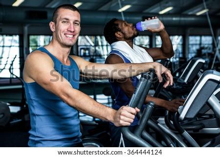 Smiling man using elliptical machine at gym - stock photo