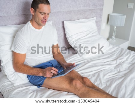 Smiling man using his tablet pc on bed at home in the bedroom