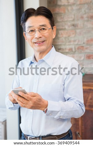 Smiling man using smartphone standing at home