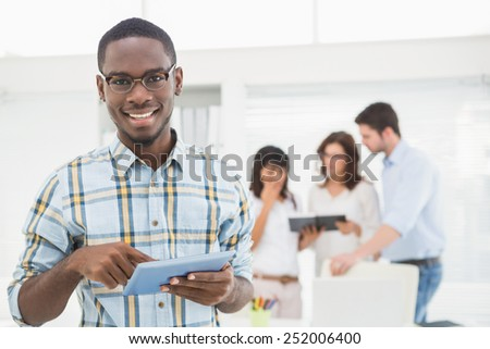Smiling man using tablet in front of his colleagues in the office - stock photo