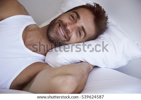 Smiling man waking in bed, portrait