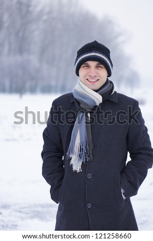 Smiling man wearing a hat in the winter - stock photo