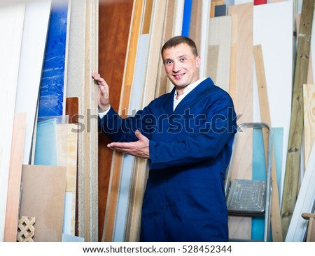 smiling man wearing protective workwear standing with plywood in store