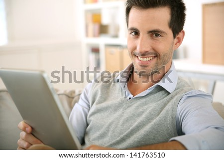 Smiling man websurfing on internet with tablet