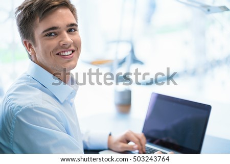 Smiling man with a laptop in office