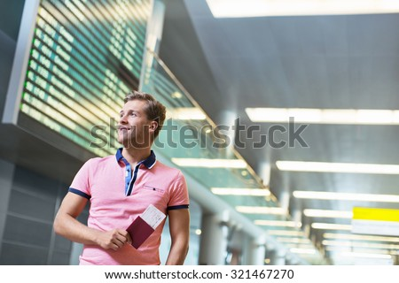 Smiling man with a passport at the airport - stock photo