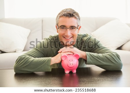 Smiling man with a pink piggy bank at home in the living room - stock photo
