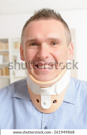 Smiling man with a surgical cervical collar  - stock photo