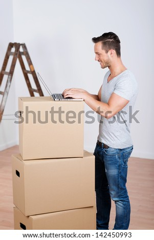 Smiling man with boxes and laptop in his new home