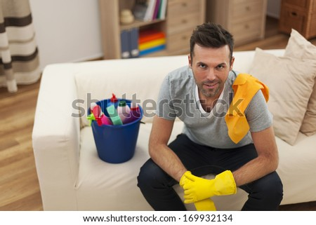 Smiling man with cleaning equipment in living room - stock photo