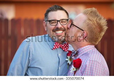 Smiling man with eyeglasses being kissed by spouse - stock photo