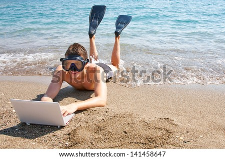 Smiling man with goggles and flippers lying on sand looking at laptop