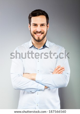 smiling man with hands folded on grey background