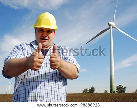 smiling man with hard hat in front of a wind park