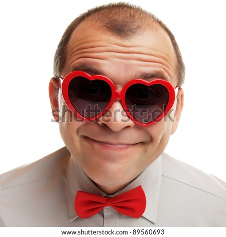 Smiling man with heart shaped sunglasses isolated on white