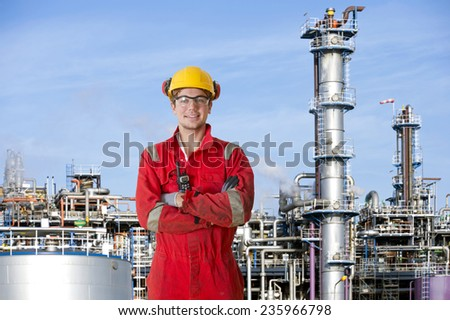 Smiling man with his arms crossed, posing in front of a large petrochemical refinery - stock photo