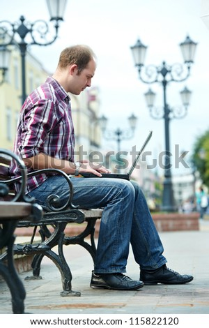 Smiling man with laptop notebook sitting on bench in the street - stock photo