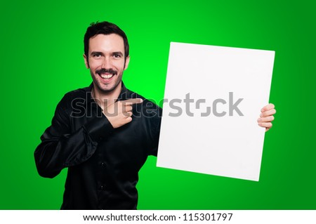 smiling man with mustache and black jacket holding blank white board on green background