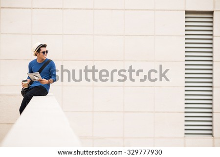 Smiling man with newspaper sitting on the balcony of office building - stock photo