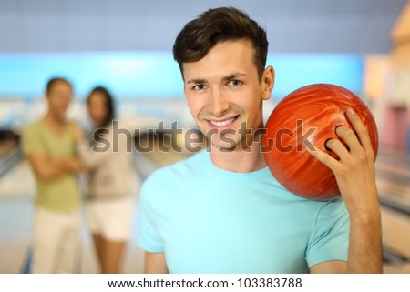 Smiling man with orange ball; couple stands behind him in bowling club; focus on right man; shallow depth of field - stock photo