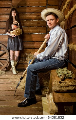 smiling man with pitchfork and in straw hat sitting on bench in wooden log hut, young woman with basket of fruit standing near wall on background - stock photo