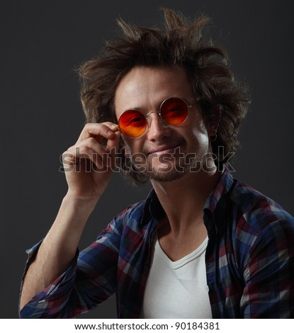 Smiling man with round hippie sunglasses and long funny hair - stock photo