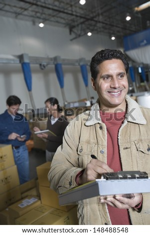 Smiling man with workers in background at distribution warehouse - stock photo