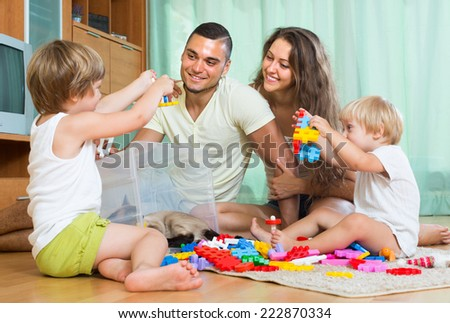 Smiling man with young wife and two daughters plays with meccano set in home