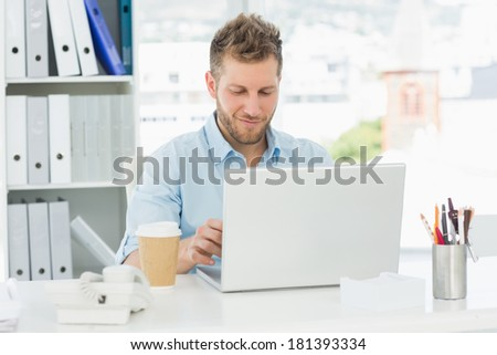 Smiling man working at his desk on laptop in creative office - stock photo