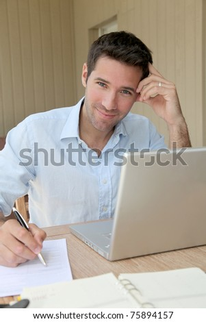 Smiling man working at home on laptop computer - stock photo