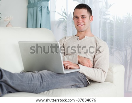 Smiling man working with his notebook in his living room