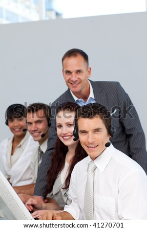 Smiling manager and his team working in a call center