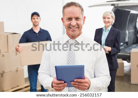 Smiling manager holding tablet in front of his colleagues in a large warehouse