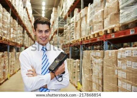 smiling manager in warehouse with bar code scanner - stock photo