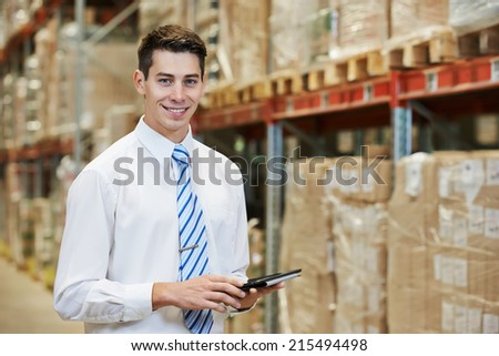 smiling manager in warehouse with tablet pc computer  - stock photo