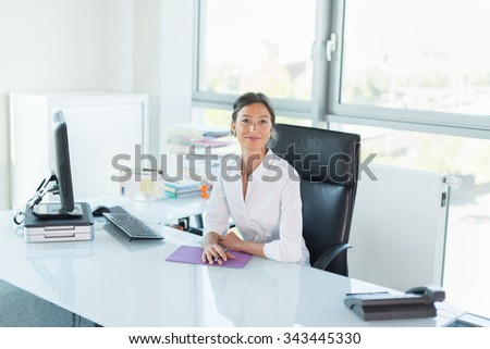 Smiling manager looking at camera in her white office Woman sitting at a tidy glass desk in front of a black computer She is wearing a white shirt her hair are tied Her hands are crossed on a folder