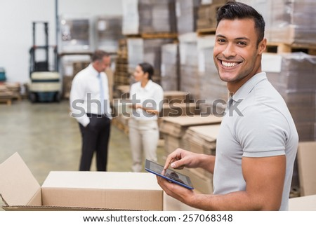Smiling manager using digital tablet in warehouse