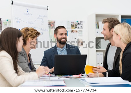 Smiling manager with his business team sitting discussing a project with them around a table with a laptop in front of him - stock photo